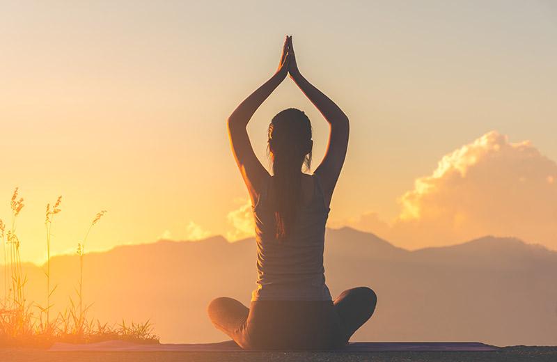 Silhouette de femme en position de yoga face au couché de soleil